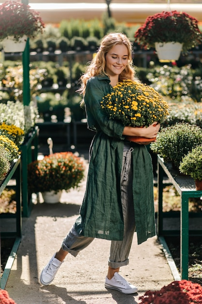 Young woman with beautiful blond hair and gentle smile, dressed in green robe with belt is working in greenhouse Free Photo