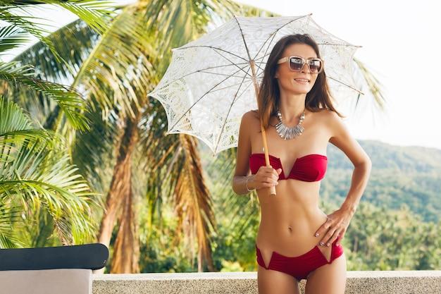アジアの休暇旅行中にトロピカルヴィラリゾートでレースの太陽傘を保持している赤いビキニ水着を着ている美しいスリムな体を持つ若い女性、細い体型、夏のスタイルのトレンドアクセサリー 無料写真