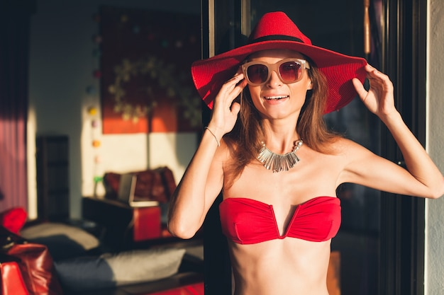 Молодая женщина с красивым стройным телом в красном купальнике бикини, соломенной шляпе и солнцезащитных очках отдыхает на тропической вилле во время отпуска в азии, худощавая фигура, модные аксессуары в летнем стиле Бесплатные Фотографии