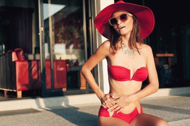 赤いビキニ水着、麦わら帽子、サングラスを身に着けている美しいスリムなボディを持つ若い女性は、アジアでの休暇中にトロピカルヴィラリゾートでリラックス、スキニーフィギュア、夏のスタイルのトレンドアクセサリー 無料写真