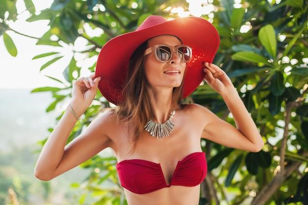 Молодая женщина с красивым стройным телом в красном купальнике бикини, соломенной шляпе и солнцезащитных очках отдыхает на тропической вилле на отдыхе на бали, худощавая фигура, аксессуары в летнем стиле, солнечно Бесплатные Фотографии