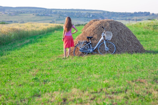 Young woman with a bicycle on field with haystacks on a sunny day Premium Photo