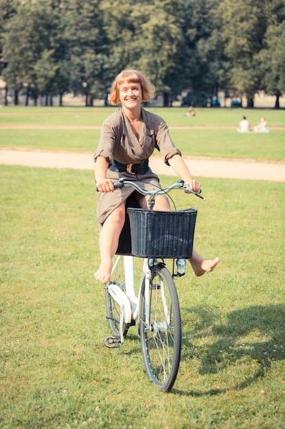Young woman with bicycle at park in vilnius Premium Photo