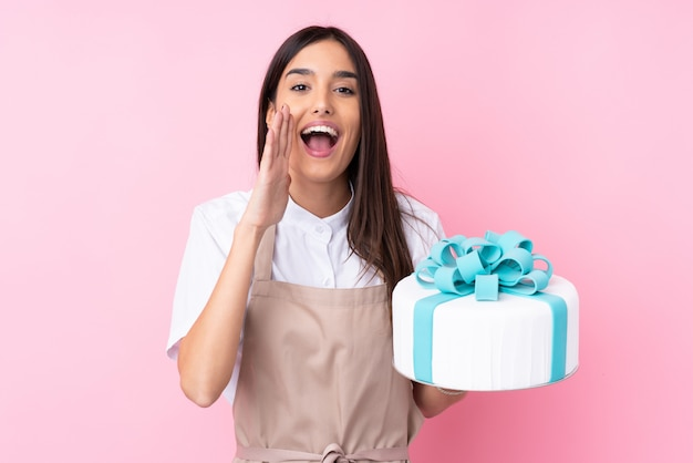 Young woman with a big cake over isolated wall shouting with mouth wide open Premium Photo