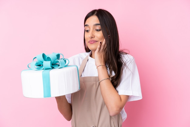 Young woman with a big cake over isolated wall Premium Photo