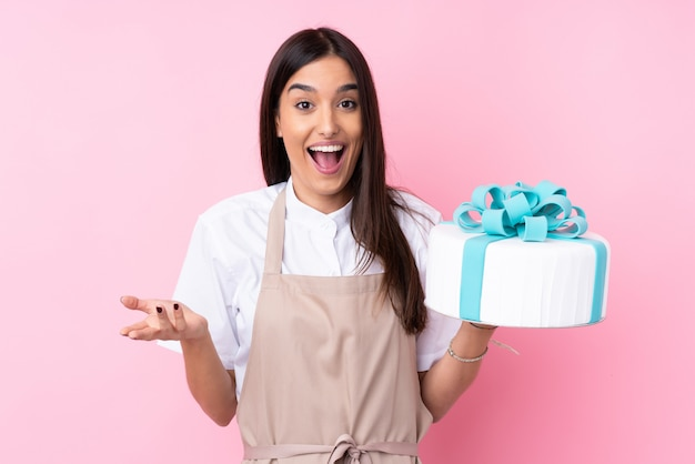 Young woman with a big cake with shocked facial expression Premium Photo