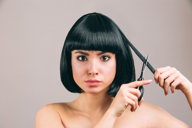 Young woman with black hair posing. serious confident brunette with bob haircut. holding scissors and cutting piece of hair. Premium Photo