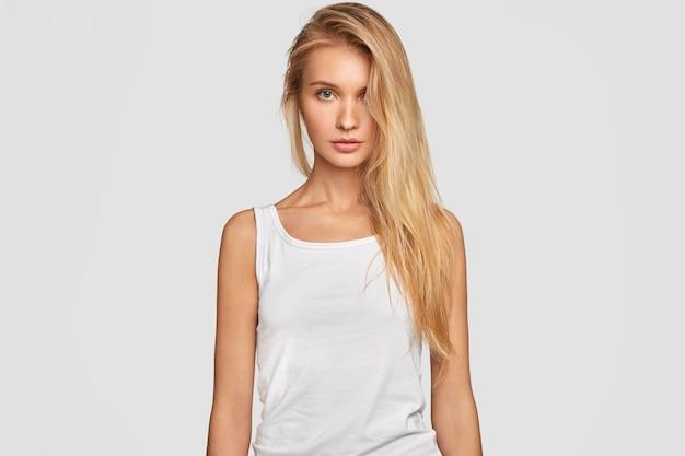 片側に金髪の長い髪をとかした若い女性は、特大のカジュアルな白いtシャツを着ています 無料写真
