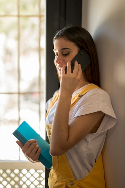 Young woman with book talking on phone Free Photo