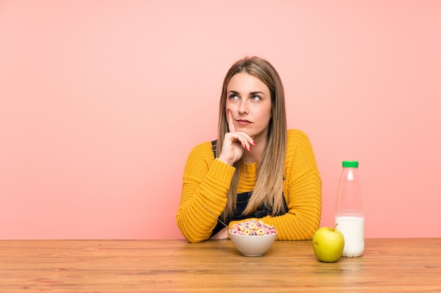Young woman with bowl of cereals thinking an idea Premium Photo