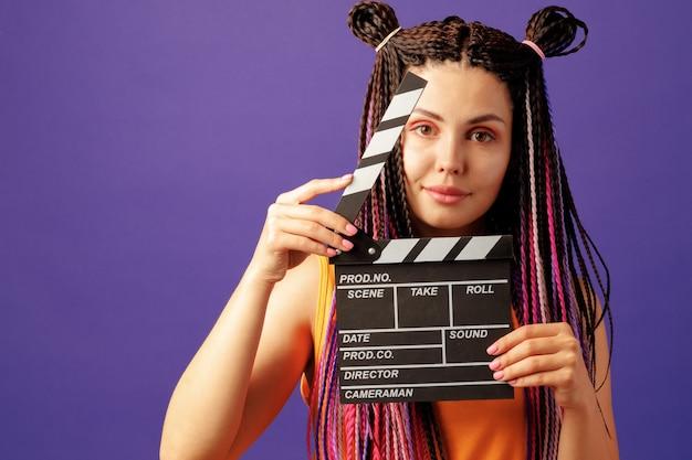 보라색 배경에 클 래퍼 보드 클로즈업을 들고 머리 띠와 젊은 여자 프리미엄 사진