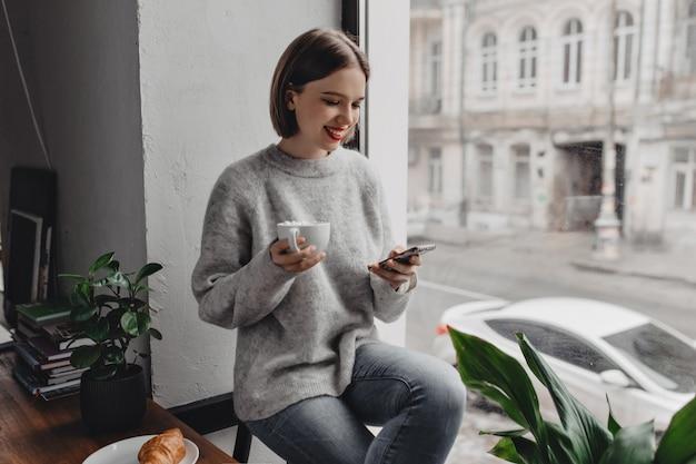 明るい口紅を持った若い女性が笑顔で電話でおしゃべりし、マシュマロとココアのカップを持って、木製のテーブルにクロワッサンと窓際でポーズをとっています。 無料写真