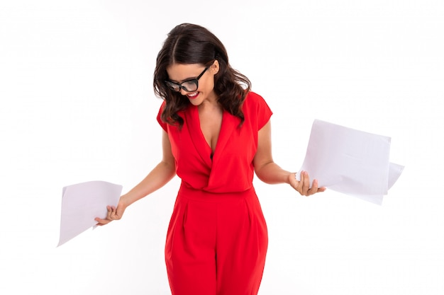 A young woman with bright makeup, in a red summer dress stands with paper and looks down Premium Photo