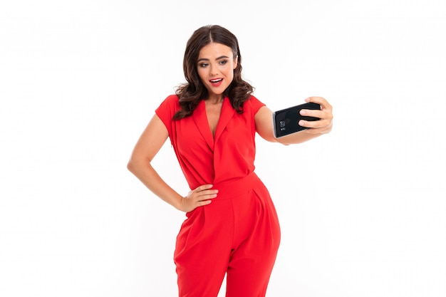 A young woman with bright makeup, in a red summer dress stands with a phone in hand and do selfie Premium Photo