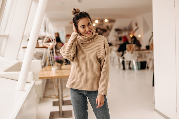 Young woman with bun and dressed in beige sweater and dark denim pants posing in cafe Free Photo