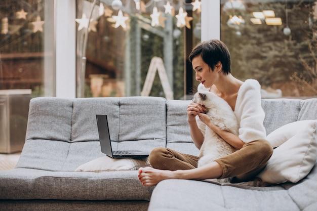 집에서 노트북에서 일하는 고양이와 젊은 여자 무료 사진
