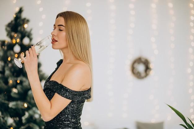 Giovane donna con champagne dall'albero di natale Foto Gratuite