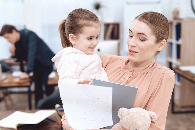 Young woman with the child came to work. Premium Photo