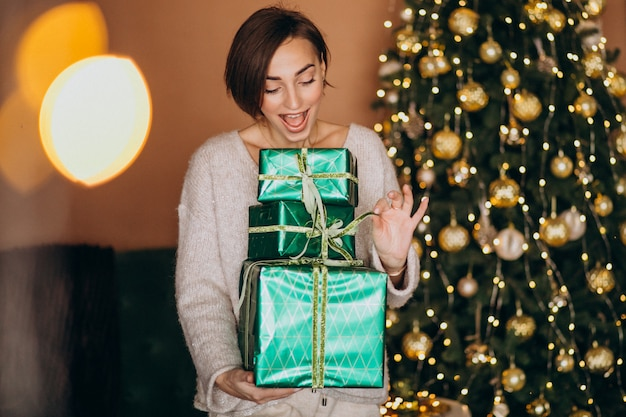 Young woman with christmas present by the christmas tree Free Photo