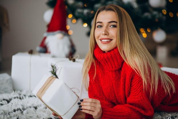 Giovane donna con regali di natale dall'albero di natale Foto Gratuite