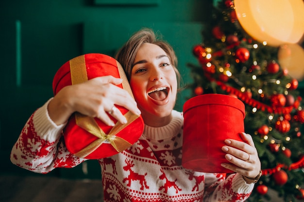 Young woman with christmas tree holding red boxes Free Photo