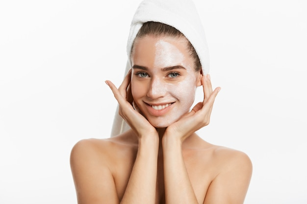 Young woman with clay facial mask, isolated on white. Premium Photo