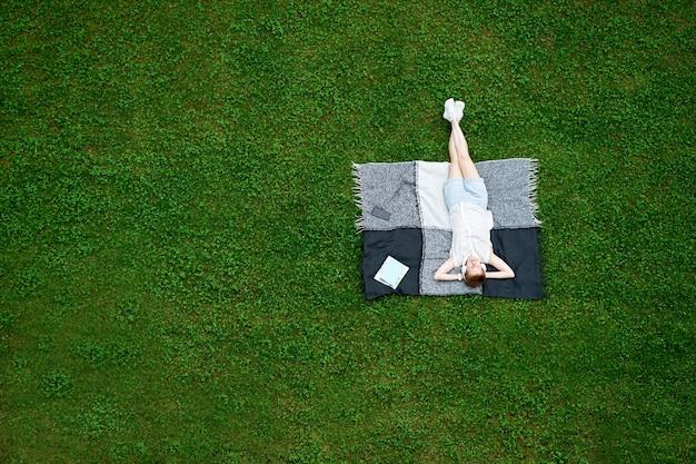 Молодая женщина с закрытыми глазами, лежа на одеяле на зеленой траве Premium Фотографии