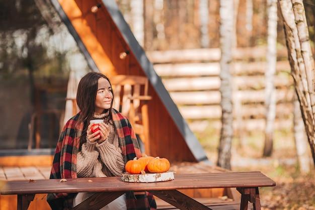 Молодая женщина с кофе, сидя за деревянным столом на открытом воздухе в осенний день Premium Фотографии