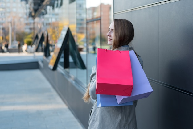 Young woman with colorful bags on the street. Premium Photo