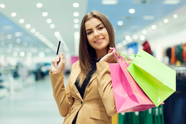 Young woman with credit card and shopping bag Free Photo