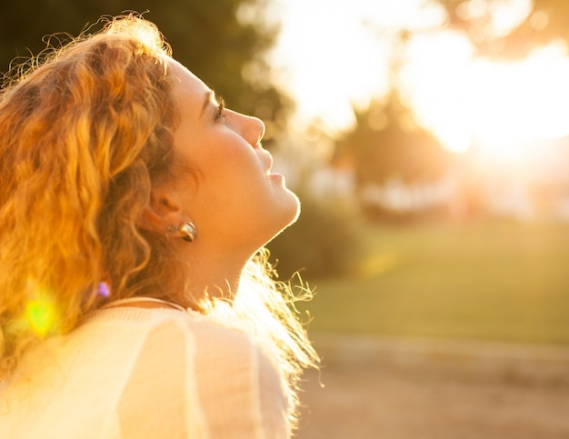 Young woman with curly hair enjoying a sunny day Free Photo