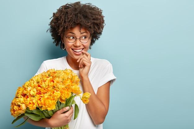 Молодая женщина с вьющимися волосами держит букет желтых цветов Бесплатные Фотографии