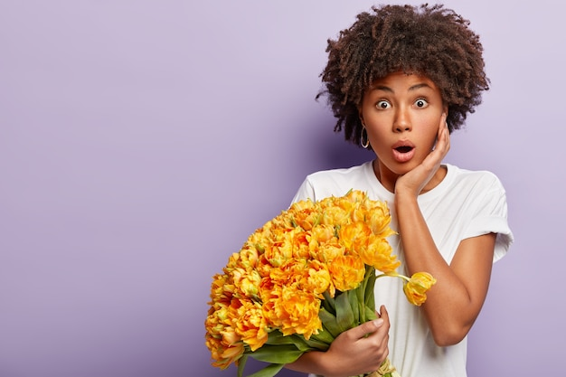 노란색 꽃의 꽃다발을 들고 곱슬 머리를 가진 젊은 여자 무료 사진