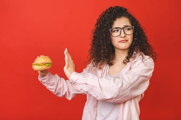 ハンバーガーを保持している巻き毛を持つ若い女 Premium写真