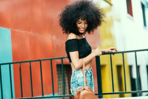 Young woman with curly hair near a modern colorful building Premium Photo