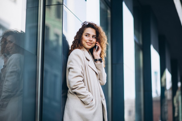 Young woman with curly hair using phone at the street Free Photo