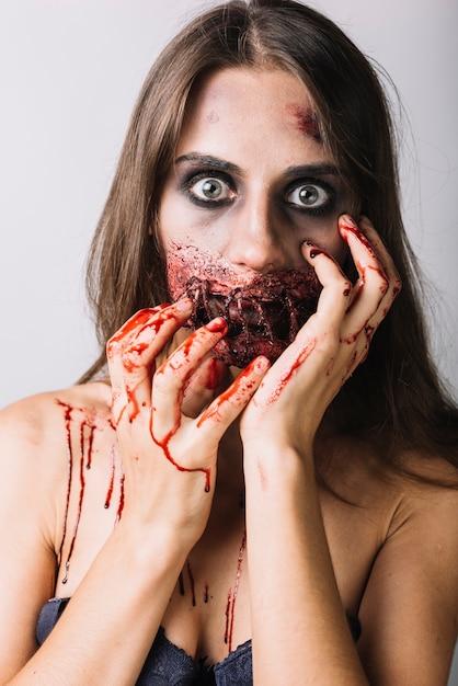 Giovane donna con viso danneggiato e mani insanguinate Foto Gratuite