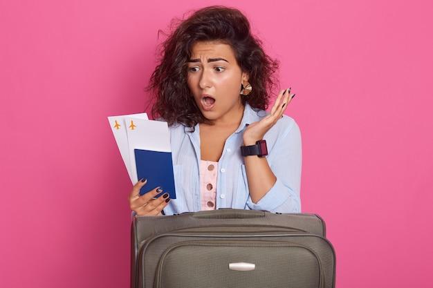 口を開いたままのカジュアルな服を着ている暗い巻き毛を持つ若い女性 Premium写真
