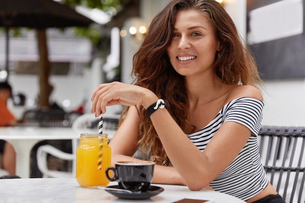 Young woman with dark long hair smiling in a coffee shop Free Photo