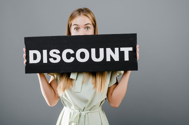Young woman with discount sign isolated over grey Premium Photo