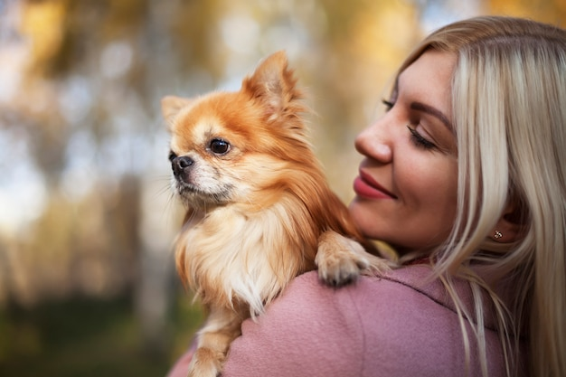 Young woman with dog in her arms on the background of beautiful nature Premium Photo