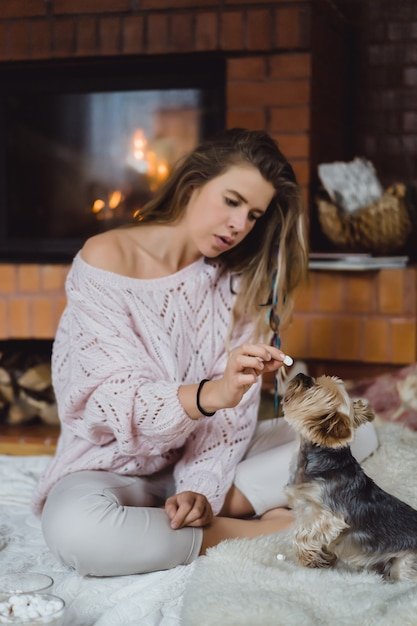 Young woman with a dog near the fireplace drinks cocoa with marshmallows. Free Photo