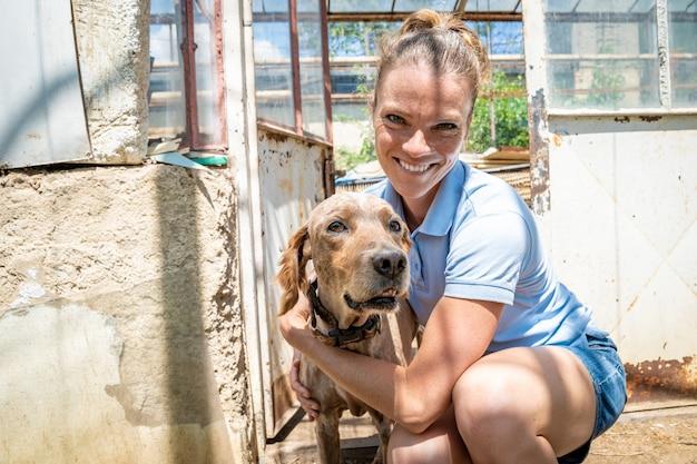농장에서 온실에서 강아지와 함께 젊은 여성 프리미엄 사진