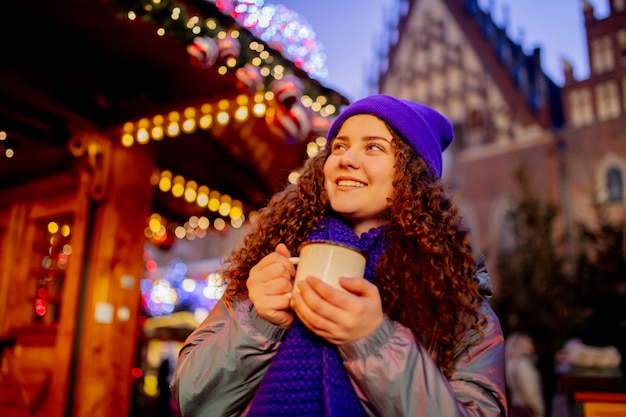 Young woman with drink on christmas market in wroclaw, poland Premium Photo