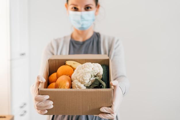 Молодая женщина с маска для лица и перчатки. доставка свежих продуктов на дом. ковид-19 карантинный шоппинг Premium Фотографии