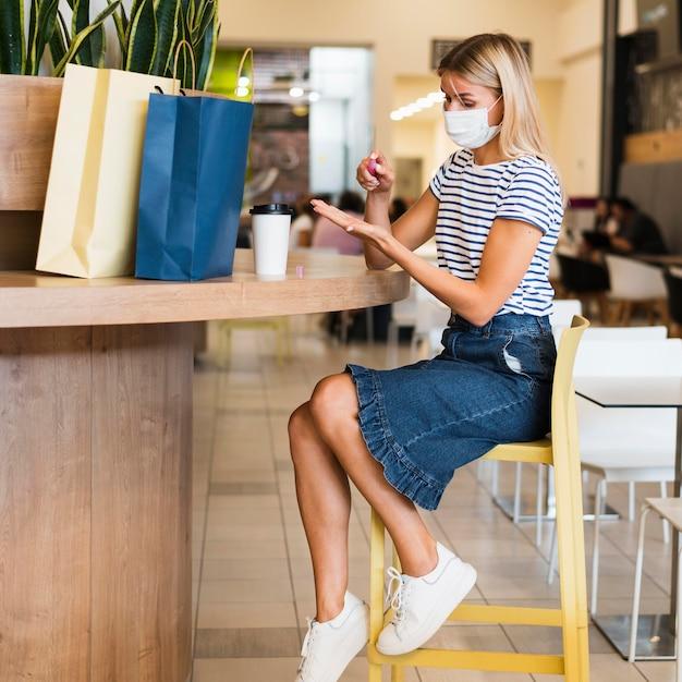 Giovane donna con la maschera per il viso che disinfetta le mani Foto Gratuite