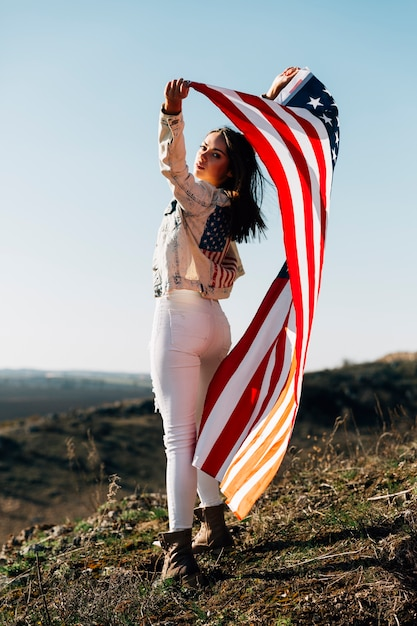 Young woman with flag standing sensually in sunlight Free Photo