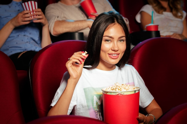 Young woman with friends watching movie in cinema Premium Photo