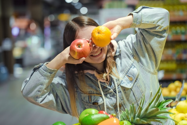 スーパーマーケットで彼女の手に果物を持つ若い女性。 無料写真