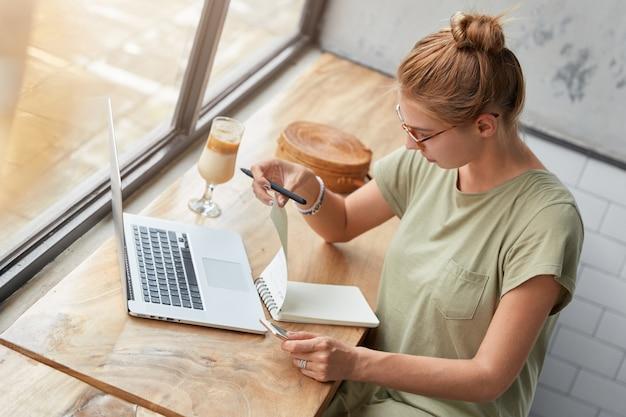 Giovane donna con gli occhiali nella caffetteria Foto Gratuite